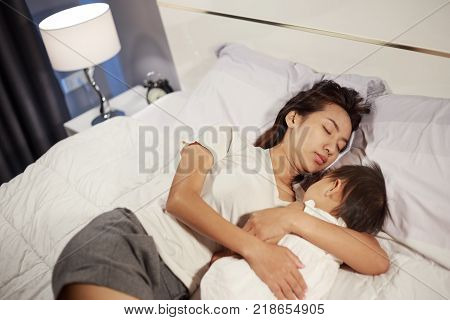 Mother And Baby Sleeping On Bed At Home