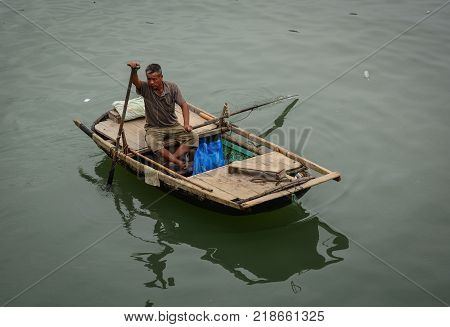 Quang Ninh Vietnam - May 23 2016. A man rowing boat on Ha Long Bay in Quang Ninh Vietnam. Ha Long Bay is a UNESCO Site and popular travel destination.