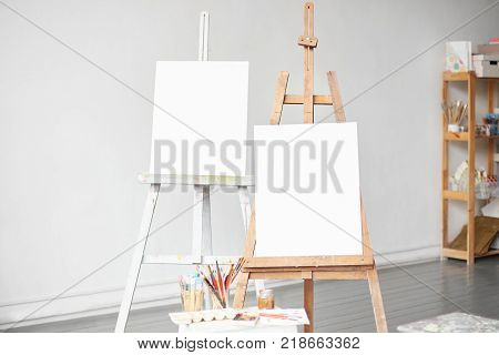 Vertical light shot of painter workplace mock up. Watercolor brushes and accessories. Two wooden easels with blank painting canvas as copy space for mock up isolated on artistic studio background.