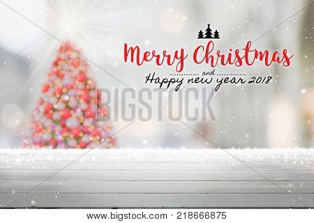 Wood table top on blur with bokeh Christmas tree background with snowfall and Merry Christmas & Happy New Year 2018 sign - can be used for display or montage your products.