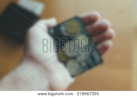 Coins and bank card in the hand, blurred defocused background photo
