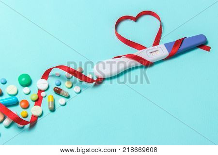 Treatment of infertility with pills help in conceiving a child. Tablets from pregnancy do not work contraception. Positive pregnancy test with two strips and a red ribbon in the form of a heart
