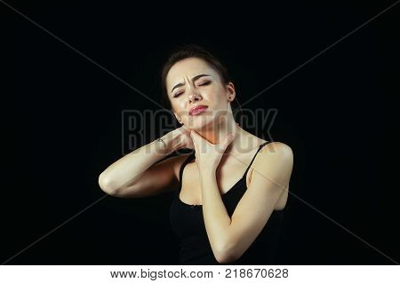 beautiful young woman hand touching her sore neck and throat . Close up of a girl suffering from a sore throat sore throat. Disease medicine and concept of health.