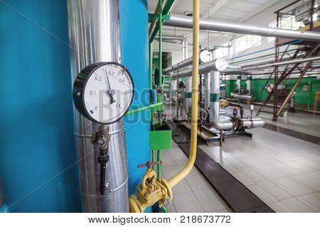 Round mechanical pressure gauges on pipelines. Modern industrial boiler room.