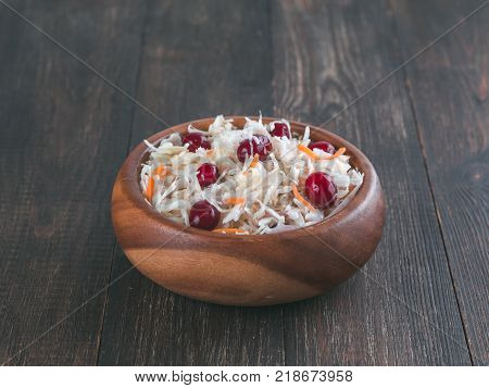 Traditional russian appetizer sauerkraut with cranberry and carrot in wooden bowl on brown rustic wooden table. Fermented cabbage. Russian cuisine and russian kitchen.
