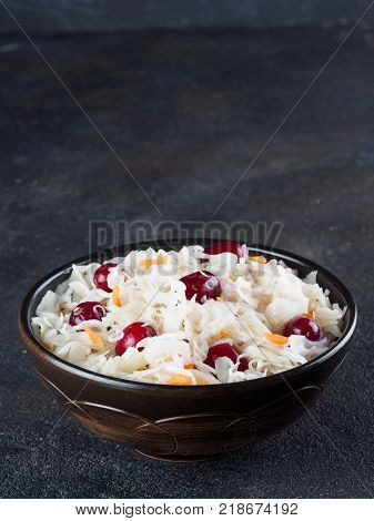 Traditional russian appetizer sauerkraut with cranberry and carrot in dark bowl on black cement background. Fermented cabbage. Russian cuisine and russian kitchen. Copy space.