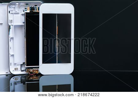 workshop on assembling smartphones on black background. free space concept. microelectronics technology.
