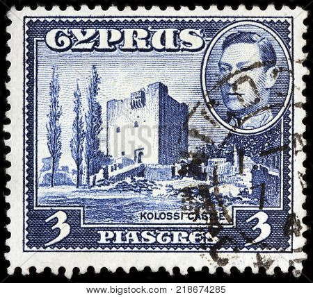 LUGA RUSSIA - OCTOBER 17 2017: A stamp printed by CYPRUS shows image portrait of King George VI and view of Kolossi Castle - a former Crusader stronghold in Kolossi village circa 1942