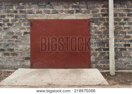 Red garage door. Garage door. Red metal door. Grunge architecture. Red door. Metal door.