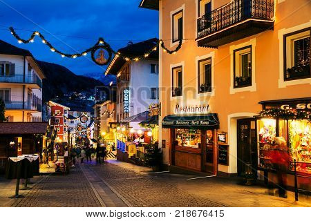 ORTISEI, ITALY - JANUARY 8, 2017: Winter night in a popular ski resort Ortisei in Italy Dolomites. Val Gardena ski resort during the night with restaurants and shops, colorful sky and decoration