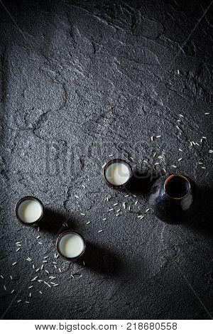 White sake in black ceramics on black rock