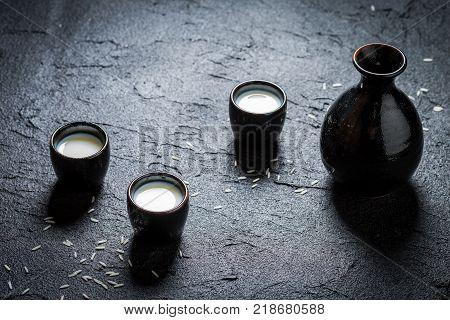 Closeup of sake in black ceramics on black rock