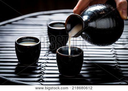 Pouring sake in to black ceramics on black table
