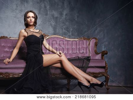 Beautiful and young girl posing in black dress on violet sofa. Vintage interior and retro background.