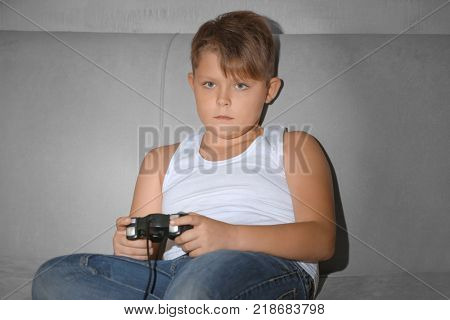Overweight boy playing video game at home
