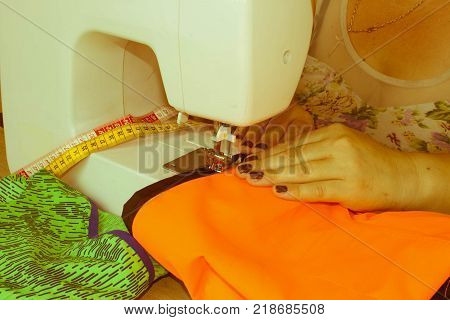 Woman hand on sewing machine.Dressmaker work on the sewing machine. Hobby sewing fabric as a small business concept. Dressmaker woman working with sewing machine - Retro color