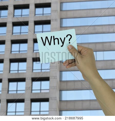 Hand of the businessman holding a paper note with Why text on high buildings background for design in your work.