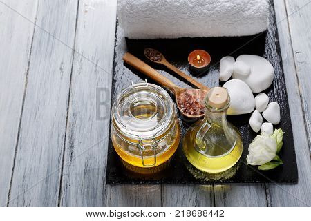 Honey, aroma oil, burning small candles, buds of beautiful white flowers and various pebbles for spa and aroma procedures on a dark stone board. View from above.