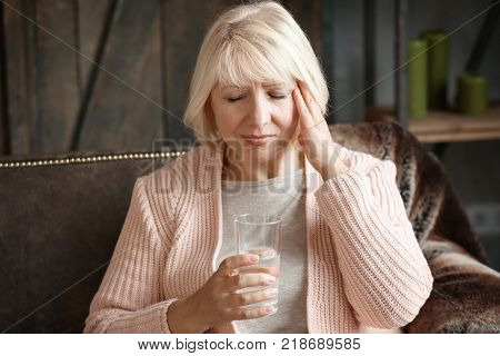 Mature woman going to take medicine for headache at home