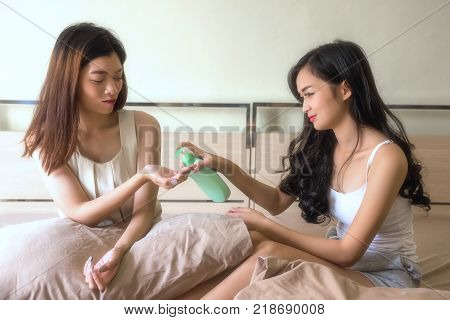 Happy Woman Friends Apply Moisture Lotion
