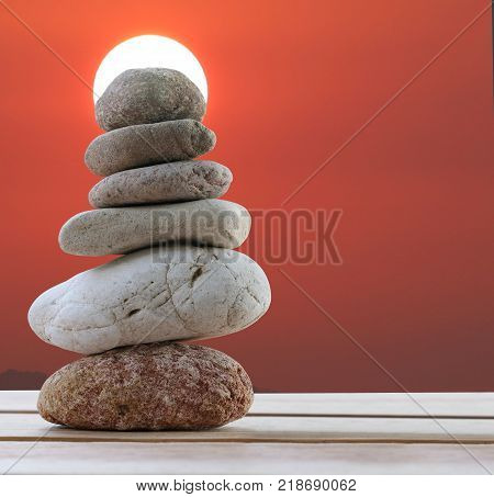 Balance Stones stacked to pyramid in the sunset background and have copy space to Spa ideas design or freedom and stability concept on rocks.