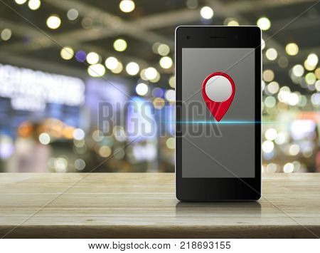 Map pin location button on modern smart phone screen on wooden table over blur light and shadow of mall Map pointer navigation concept