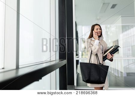 Attractive and beautiful businesswoman standing in office talking on cellphone