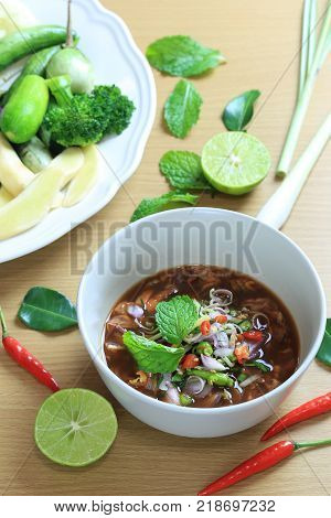 Pickled mussels of thai foods with spicy salad in a bowl on wooden floorThis food has been popular in Thailand.