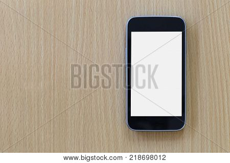 Empty Screen of Smartphone placed on a brown wooden floor and have copy space to input ideas of your work.