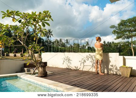 Young woman wearing towel relaxing near swimming pool at exotic location