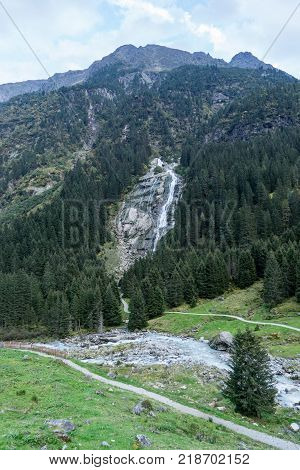Mountain river and trees landscape natural environment. Hiking in the alps. Grawa Waterfall in Stubai Valley, Tyrol, Austria