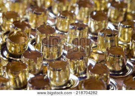 Golden eyelets lying rows rivets loose close-up
