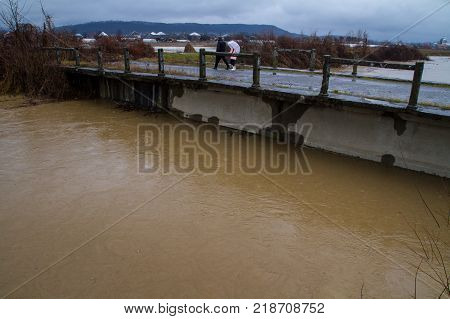 Syltse Ukraine - December 16 2017: A local man with his daughter looks at the water level from the old bridge during the winter flood near the village of Syltse.