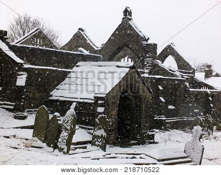 picturesque ruined church in falling snow in heptonstall with graveyard and arches
