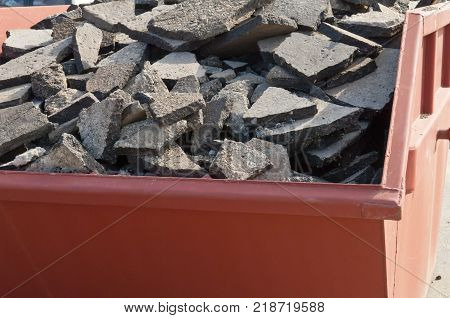 Waste asphalt pavement and concrete materials in waste container