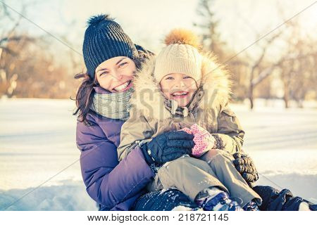 Little girl and her mother playing outdoors at sunny winter day