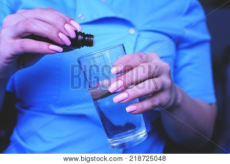 A young girl, the nurse puts drops in a glass of water. The treatment of poisoning