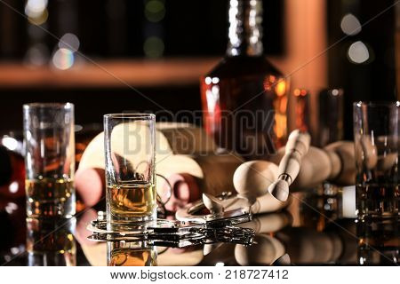 Composition of glassware and toy car with handcuffs on table in bar. Don't drink and drive concept