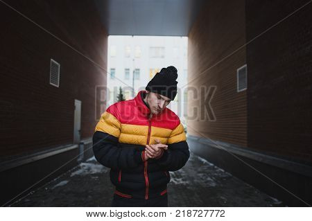 Strong big dangerous man in gateway. Winter time. Street mugger. Social concept of submission.