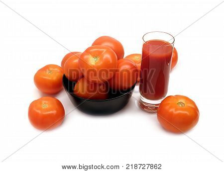 Big glass with tomato juice and many ripe tomatoes in round black bowl studio shot isolated on white background