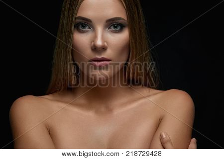 Horizontal studio portrait of a beautiful young woman posing sensually embracing herself on dark background beauty femininity seduction sensuality elegance confidence vulnerability concept.