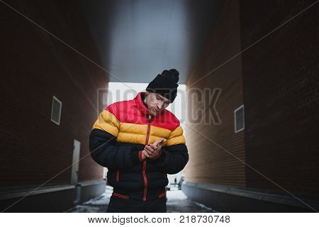 Stylish man in a down coat, on the gateway urban background.