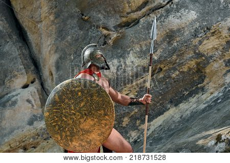 Portrait of a brave medieval warrior in a helmet and red cloak holding a shield and a spear resting outdoors on top of a rock copyspace bravery power courage masculinity defence armor.