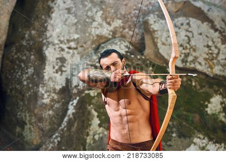 Horizontal shot of a muscular mature Spartan wearing red cloak shooting from a bow with arrows copyspace archer archery weapon armed attack hunting hunter medieval historic gym strength.
