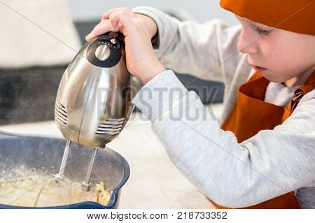 The boy in the orange clothes of the cook mixes the products for dough with a mixer in a large cup.