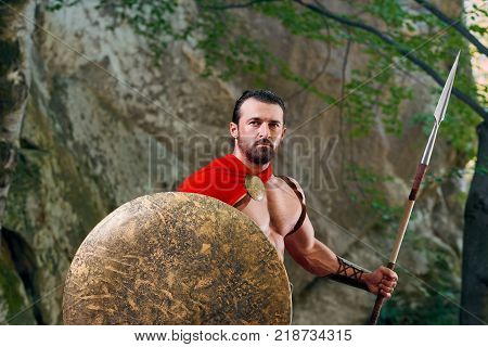 Handsome mature Spartan soldier with a shield and a spear looking to the camera seriously standing outdoors near the rock copyspace bravery masculinity confidence power strength.
