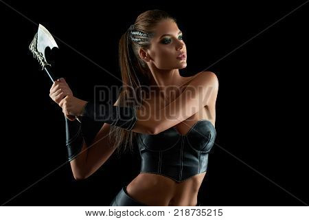 Horizontal shot of a stunning female fighter in leather traditional Amazons tribe battledress posing fiercely with an axe on black background historical culture warrior protector sexy. poster