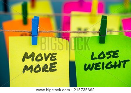 A set of colorful sticky notes with positive affirmation words and phrases hung from a clothesline by clothespins. These include: Move More and Lose Weight