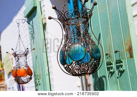 Two lamps made of wire filigree hanging from green shutters outside a white building. One lamp sports blue glass discs as decoration and the other orange discs. Bright sun shines on them from a blue sky.