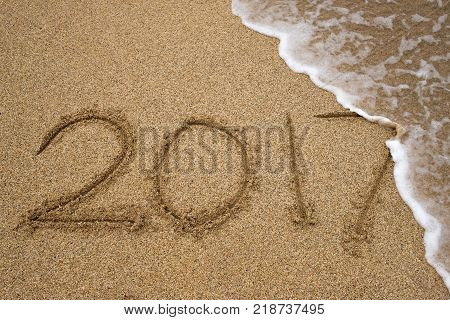 Number 2017 written on seashore sand. Concept of upcoming new year and passing of time.